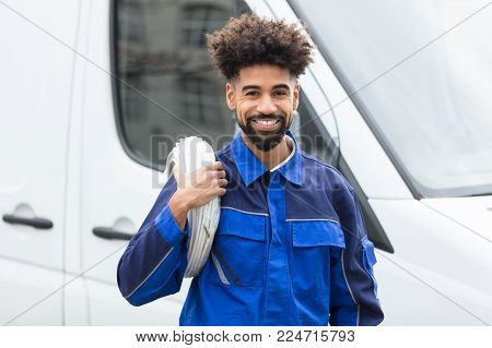 Portrait Of Smiling Electrician With White Cable Coil Standing By Van