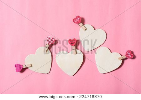 White hearts with pink clothes pegs (heart shape) on pink background, Valentine concept