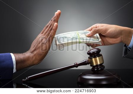 Close-up Of A Judge's Hand Refusing Bribe From A Client Against Gray Background