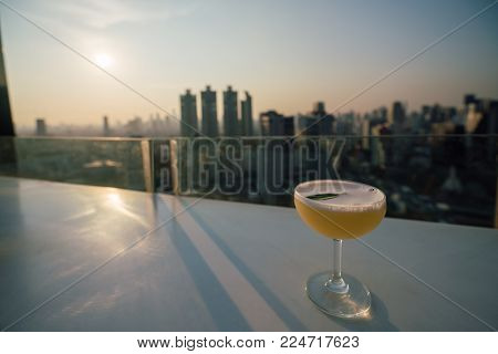 Sunset Scene Of Cocktail Put On Table At Rooftop Sky Bar In Bangkok City Thailand.