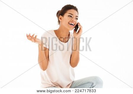 Photo of mixed race woman in casual smiling and speaking on cellphone isolated over white background