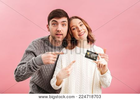 Portrait of a happy loving couple dressed in sweaters holding credit card and pointing finger isolated over pink background