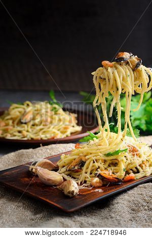 Italian pasta in a creamy sauce with seafood, shrimps and mussels on a fork on a dark wooden background