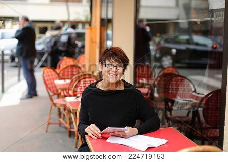 Business woman sitting at table in street cafe, fill declaration with tablet and sheets of paper. Lady dressed in black blouse have contented expression. Female hold white gadget and pen, compares data. Concept of benefit from modern compact gadgets.