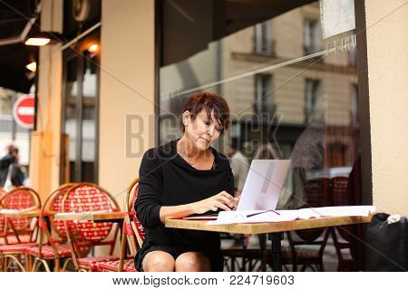aged female screenwriter sitting in outdoor cafe and reproduce scenario from paper drafts in text file on laptop. Lady dressed in black cardigan looks like very pleased with work. Woman scans pages and removes lying glasses aside.