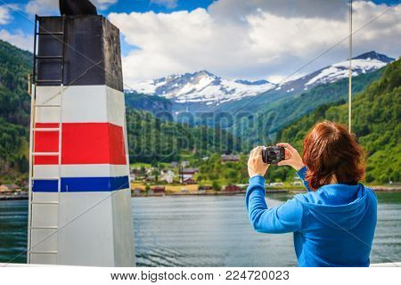 Tourism vacation and travel. Tourist woman on cruise ship enjoying fjord view, taking photo with camera. Norway Scandinavia Europe. Norddalsfjorden as seen from ferry.