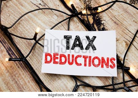 Handwritten text caption showing Tax Deductions. Business concept writing for Finance Incoming Tax Money Deduction written on the wooden background.