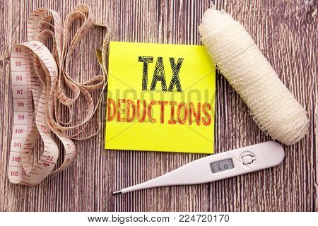 Tax Deductions. Business fitness health concept for Finance Incoming Tax Money Deduction written on wood wooden background with bandage and thermometer