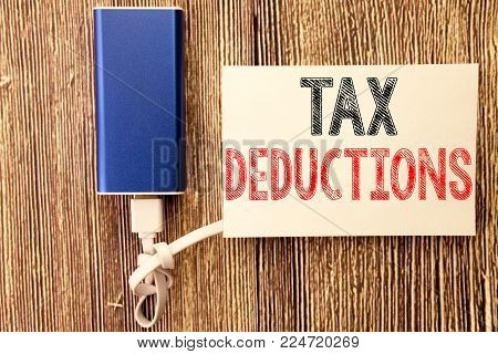 Conceptual hand writing text caption inspiration showing Tax Deductions. Business concept for Finance Incoming Tax Money Deduction written on sticky note wood wooden background with power bank