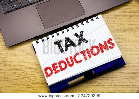 Hand writing text caption inspiration showing Tax Deductions. Business concept for Finance Incoming Tax Money Deduction written on notebook book on wooden background in the Office with laptop