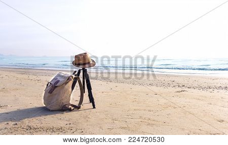 View of the sandy beach with a brown hat and knapsack on the beach near the sea. The swash of seawater up the beach after the breaking of a wave. Background with copy space and visible sand texture.