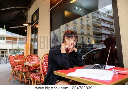 Aged grandmother sitting with laptop in outdoor cafe and have conversation  with grandchildren by videomessanger . Relatives not communicate for long time, and lady looking very happy. Female smiling  watching children. Concept of communication via innova