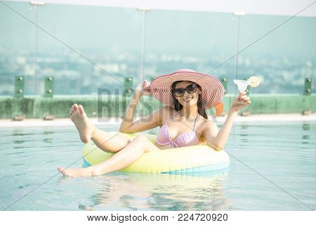 Asian Woman Floating On Float Swim Ring In Swimming Pool. Woman With Enjoyment At Swimming Pool.