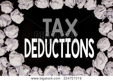 Word, writing Tax Deductions. Business concept for Finance Incoming Tax Money Deduction written on black background with copy space on background with folded paper balls