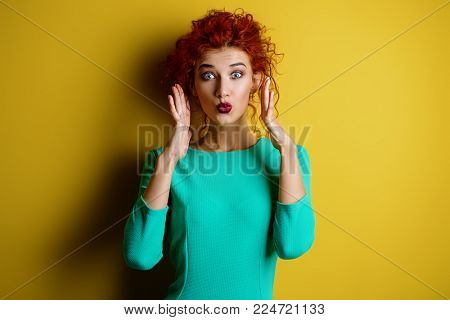 Portrait of a beautiful emotional young woman with curly foxy hair wearing blue dress over yellow background.  Beauty, fashion concept. Make-up and cosmetics. Studio shot.