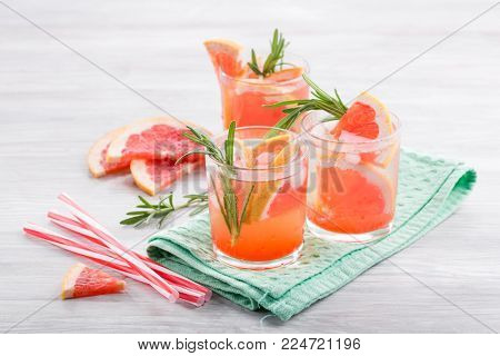 Grapefruit juice with rosemary and ice in a glass on the table. Refreshing summer cocktail