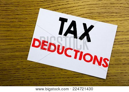 Tax Deductions. Business concept for Finance Incoming Tax Money Deduction written on sticky note, wooden background with copy space.