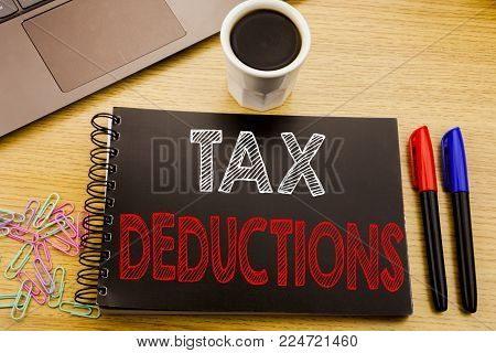 Handwriting Announcement text showing Tax Deductions. Business concept for Finance Incoming Tax Money Deduction written on notebook book on wooden background in the Office with laptop coffee