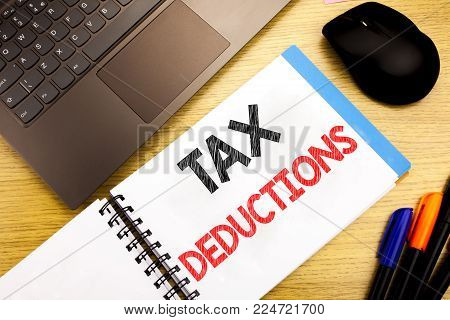 Handwritten text caption showing Tax Deductions. Business concept writing for Finance Incoming Tax Money Deduction written on notepad with space on old wood wooden with pen computer