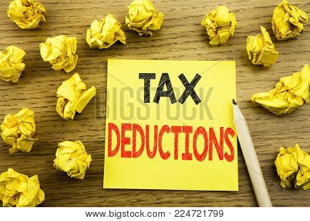Word, writing Tax Deductions. Business concept for Finance Incoming Tax Money Deduction written on sticky note paper on wooden background. Folded yellow papers on the background