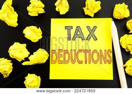 Handwritten text showing Tax Deductions. Business concept writing for Finance Incoming Tax Money Deduction written on sticky note paper on black background. Folded yellow papers on the background