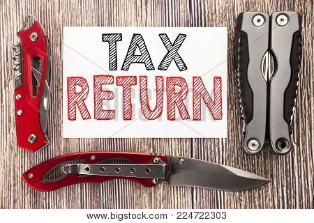 Conceptual hand writing text caption inspiration showing Tax Return. Business concept for Accounting Money Return written on old wooden background with pocket knife with space