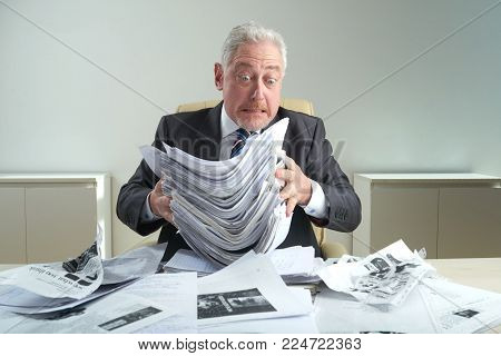 Surprised aged white collar worker wearing classical suit holding pile of documents in hands while sitting at office desk covered with crumpled paper