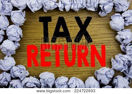 Handwriting Announcement text showing Tax Return. Business concept for Accounting Money Return written on wooden wood background with on old background with folded paper balls