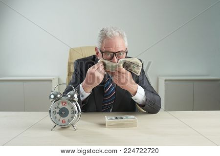 Waist-up portrait of wealthy senior businessman looking at camera while sniffing bundle of freshly printed banknotes, alarm clock standing on office desk