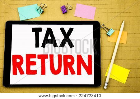Hand writing text caption inspiration showing Tax Return. Business concept for Accounting Money Return Written on tablet, wooden background with sticky note and pen