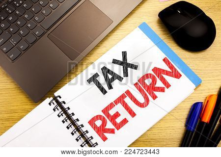 Handwritten text caption showing Tax Return. Business concept writing for Accounting Money Return written on notepad with space on old wood wooden with pen computer