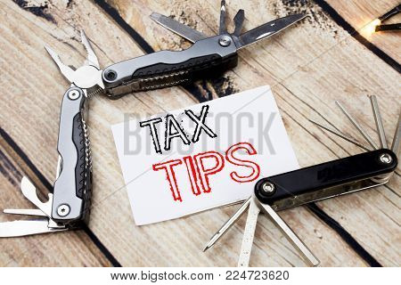 Conceptual hand writing text caption inspiration showing Tax Tips. Business concept for Taxpayer Assistance Refund Reimbursement written on old wooden background with pocket knife with space