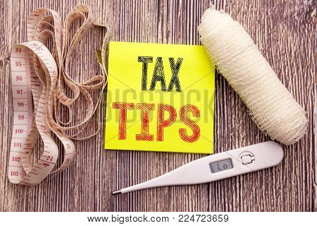 Tax Tips. Business fitness health concept for Taxpayer Assistance Refund Reimbursement written on wood wooden background with bandage and thermometer