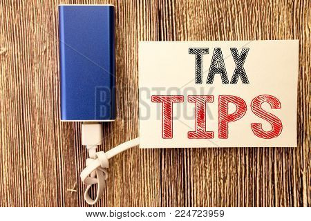 Conceptual hand writing text caption inspiration showing Tax Tips. Business concept for Taxpayer Assistance Refund Reimbursement written on sticky note wood wooden background with power bank
