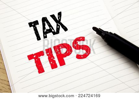 Tax Tips. Business concept for Taxpayer Assistance Refund Reimbursement written on notebook with space on book background with marker pen