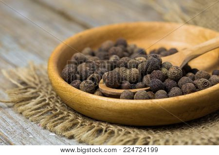 Black Pepper Peas In A Spoon On A Wood Background. Black Pepper Peas In A Spoon On A Wood Background