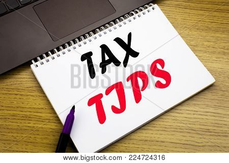 Hand writing text caption inspiration showing Tax Tips. Business concept for Taxpayer Assistance Refund Reimbursement written on notebook book on wooden background in the Office with laptop