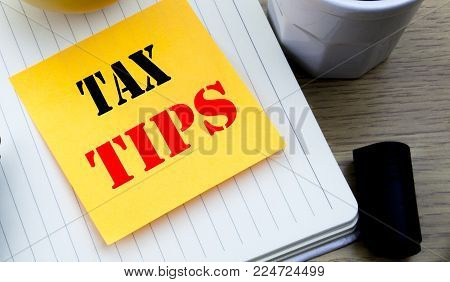 Writing text showing Tax Tips. Business concept for Taxpayer Assistance Refund Reimbursement written sticky note paper, Wooden background with copy space, Coffee and marker