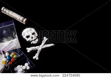 Drug dependence Kills. A line of cocaine in the form of a skull and a roll of a dollar, sachets with a dose, pills. Black background. Addiction concept. Copy space for text