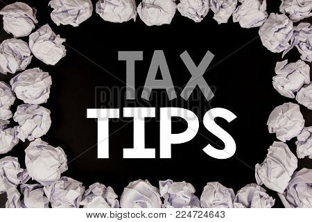 Word, writing Tax Tips. Business concept for Taxpayer Assistance Refund Reimbursement written on black background with copy space on background with folded paper balls