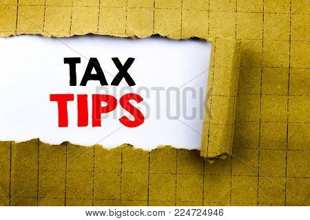 Word, writing Tax Tips. Business concept for Taxpayer Assistance Refund Reimbursement written on white paper on yellow folded paper.