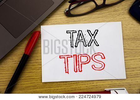 Handwriting Announcement text showing Tax Tips. Business concept for Taxpayer Assistance Refund Reimbursement written on paper, wooden background in office copy space, marker pen and glasses