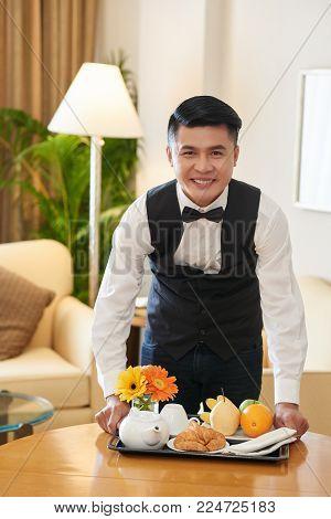 Handsome Vietnamese waiter bringing breakfast to the hotel room