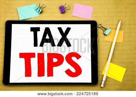 Hand writing text caption inspiration showing Tax Tips. Business concept for Taxpayer Assistance Refund Reimbursement Written on tablet, wooden background with sticky note and pen