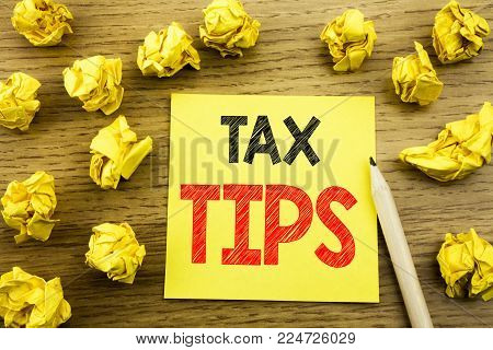 Word, writing Tax Tips. Business concept for Taxpayer Assistance Refund Reimbursement written on sticky note paper on wooden background. Folded yellow papers on the background