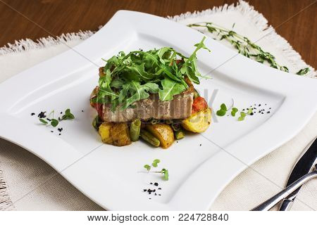 Baked fish fillets with potatoes and green beans on a square plate
