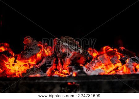 Ember in the fireplace with dark background. Close up shot.