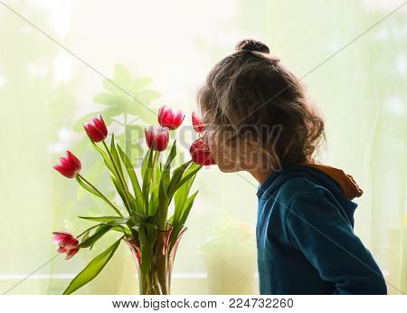 Little Adorable Girl With Bouquet Of Tulip Flowers.