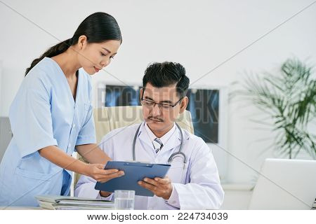 Nurse bringing medical history to young doctor