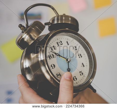Hand holding silver alarm clock counting down to 7 o clock